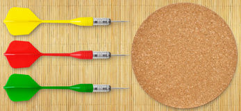Three colored darts and a cork circle Stock Images