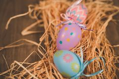 Three colored easter eggs on bed of straw stock images