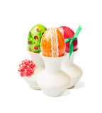 Three colored easter eggs in cup with ribbon on white background Stock Photos