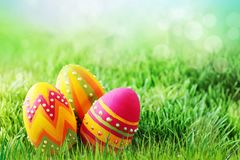 Three colored easter eggs on the grass royalty free stock photo