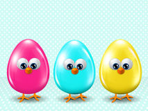 Three colored Easter eggs standing onblue dotted background Royalty Free Stock Photos