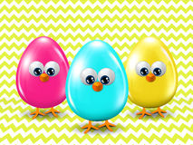 Three colored Easter eggs standing ongreen zigzag background Stock Photography