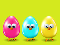 Three colored Easter eggs standing on spring green background Stock Images