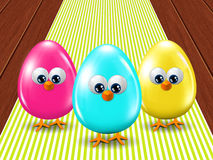 Three colored Easter eggs standing on tablecloth Stock Photos