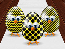 Three colored Easter eggs standing on tablecloth Royalty Free Stock Photos
