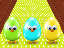 Three colored Easter eggs standing on wooden floor Royalty Free Stock Photography