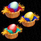 Three colored eggs closeup in straw baskets Royalty Free Stock Photos