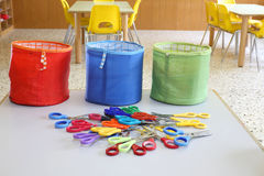 Three colored fabric containers for toys and lots of scissors in Stock Photography