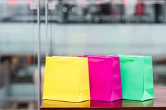 Three colored gift bags in a mall with a defocused background. royalty free stock image