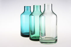 Three colored glass bottles on white background royalty free stock images