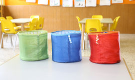 Three colored jars for toys in kindergarten classroom Royalty Free Stock Photos