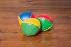 Three colored juggling balls. In a triangle on a wooden table Stock Photography