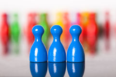 Three colored ludo figures in front of many others Stock Photo