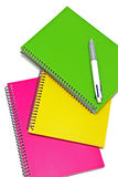 Three colored notebooks with a pen on white background Stock Photo