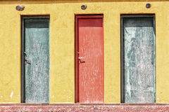 Three colored old wooden door and yellow wall Stock Image