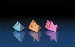 Three colored paper boats. Three ships of different colored paper on blue and black background royalty free stock images