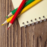 Three colored pencils and notebook on wooden table. Royalty Free Stock Photo