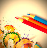 Three colored pencils and shavings Royalty Free Stock Photos