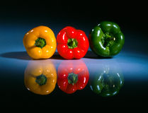 Three colored pepers on a table 2 Stock Photos