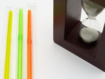 Three colored plastic straws and a hourglass. White background with empty space for caption. Plastic straws are being banned in various countries around the stock photography
