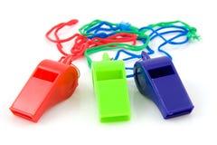 Three colored plastic whistles stock photo