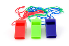 Three colored plastic whistles stock images