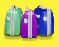 Three colored suitcases. Three bright colored suitcases on yellow isolated background with clipping path supplied Stock Images