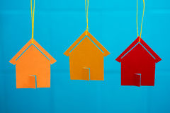 Three colored toy houses. Toy houses hanging from a rope on the background wall with blurred background Stock Photography