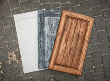 Three colored wooden doors lying on paving road Stock Photos