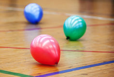 Three colorful balloons in a sports hall Stock Photography