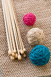 Three colorful balls and wooden needles lying on beige Royalty Free Stock Images