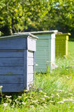 Three colorful beehives in a row Royalty Free Stock Image
