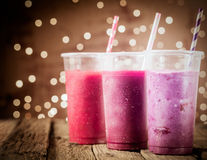 Three colorful berry smoothies with party lights. Three different colorful berry smoothies with twinkling party lights standing in a row on a rustic wooden royalty free stock photos