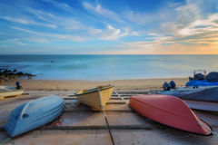 Three colorful boats resting on the shore. Stock Photos