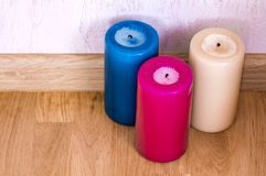 Three colorful candles on wooden floor Royalty Free Stock Photo