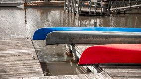 Three colorful canoes resting upside down on a dock royalty free stock photos