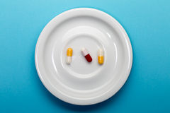 Three colorful capsules on a plate Stock Photos