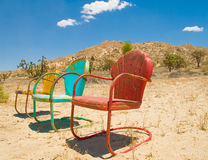 Three Colorful Chairs Forgotten In the Desert stock images