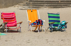 Three colorful chairs on the sand, near the beach Royalty Free Stock Image