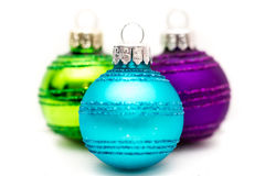 Three colorful Christmas baubles over white Royalty Free Stock Image