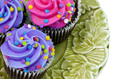 Three colorful cupcakes on plate Stock Images