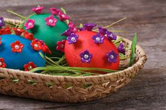 Three colorful Easter eggs with beautiful flowers in a basket Stock Images