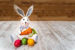Three colorful Easter eggs in front of Easter bunny with wooden background stock photography