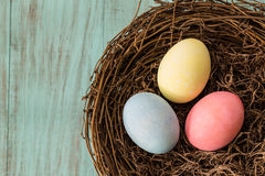 Three Colorful Easter Eggs In A Nest. On blue wooden background Stock Photography