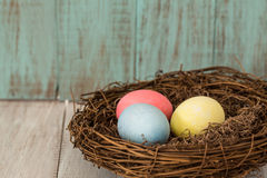 Three Colorful Easter Eggs in a Nest. On blue wooden background Royalty Free Stock Photo