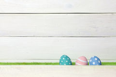 Three colorful handmade easter eggs stand on a green lawn, covered with a barrier, on a white wooden background with space on the Royalty Free Stock Photo