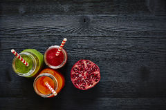 Three colorful juices on dark wooden surface with pomegranate Stock Image