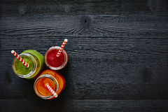 Three colorful juices with straws on dark wooden surface Royalty Free Stock Images