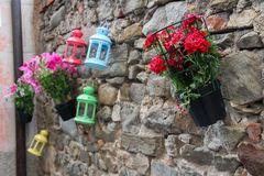 Three colorful lanterns with three geraniums, one red and one pink stock photos