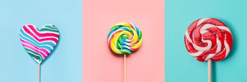 Three colorful lollipops candy as heart and swirl on blue and pink. Top view. Collage. Three colorful lollipops candy as heart and swirl on blue and pink. Funny royalty free stock photography